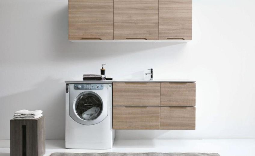Simple pretty laundry room decor design with washing machine beside wooden vanity cabinet as well gray rug on white tile floor