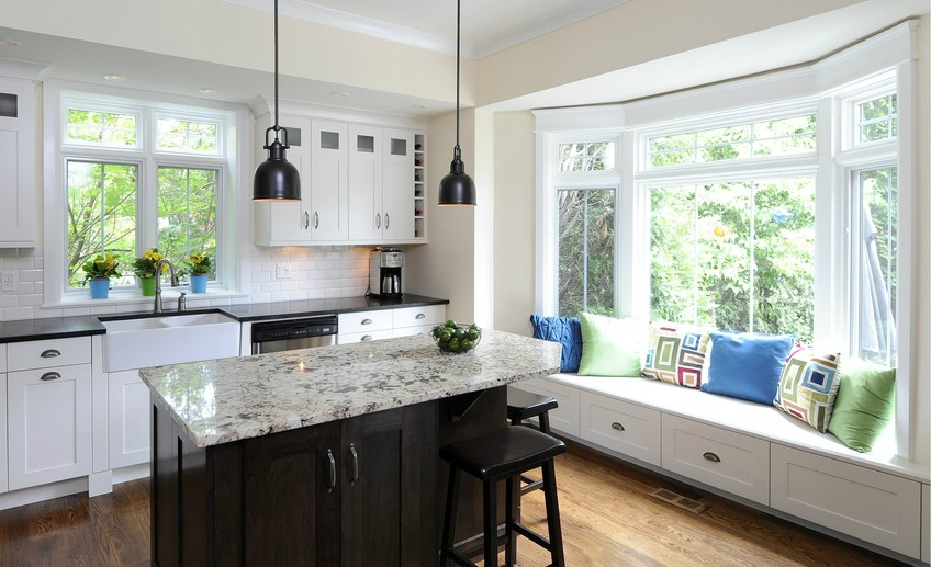 Usual gorgeous bay window seat with white shaker cabinets and transom windows plus black kitchen island and granite countertops also pendant lighting and wood floor