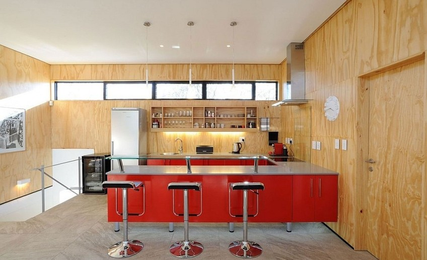 Usual lem piston bar stools and a ravishing red kitchen peninsula enliven the space